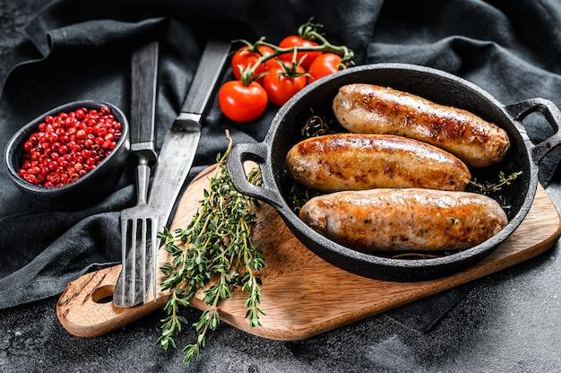 Lekkere zelfgemaakte worstjes in een koekenpan. varkensvlees, rundvlees en kippenvlees. zwarte achtergrond. bovenaanzicht.