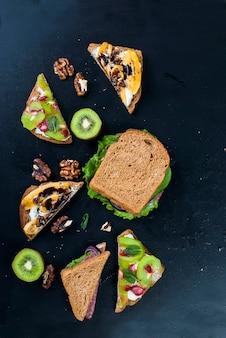 Lekkere zoete broodjes met bananen, noten en chocolade, kiwi, aardbeien en mint op zwarte achtergrond