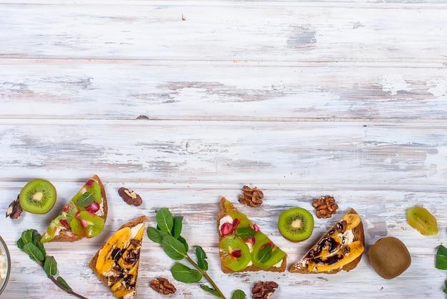 Lekkere zoete broodjes met bananen, noten en chocolade, kiwi, aardbeien en munt op houten tafel