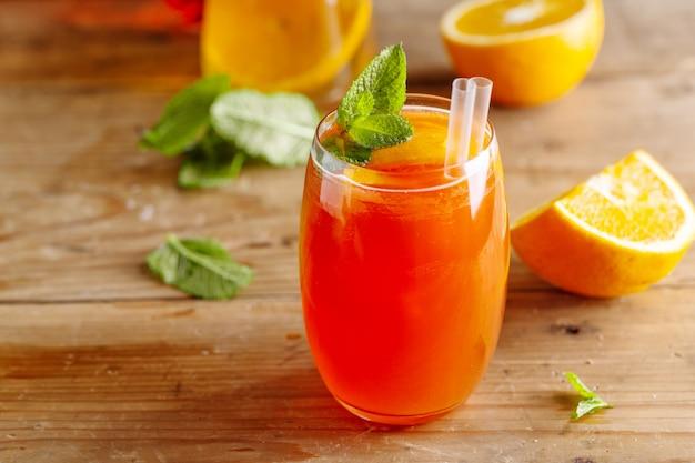 Lekkere zoete frisse verfrissende zomercocktail met sinaasappels en munt geserveerd in glas. detailopname