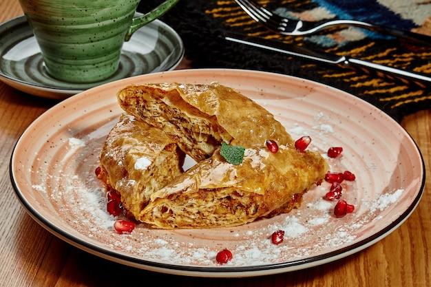 Lekkere zoete gerolde baklava gedrenkt in honingsiroop met walnoten gegarneerd met poedersuiker, granaatappelpitjes en verse munt geserveerd met koffie in georgisch restaurant. traditioneel nationaal dessert