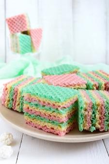 Lekkere zoete kleurrijke luchtwafelcake en cappuccinokopje op witte houten tafel