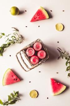 Lekkere zomer gebotteld watermeloen drankje in een mand en plakjes vers fruit op witte achtergrond
