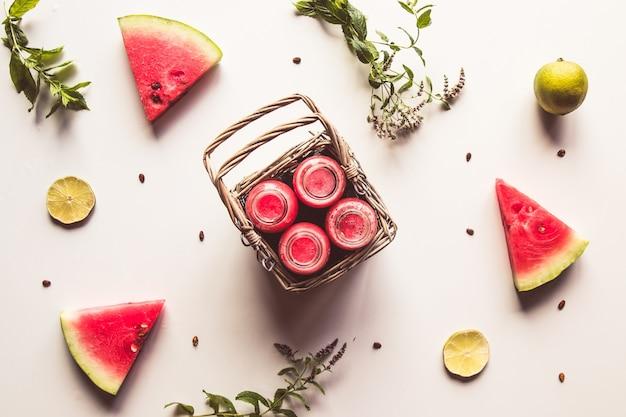 Lekkere zomer gebotteld watermeloen drankje in een mand en plakjes vers fruit