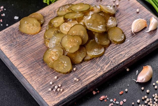 Lekkere zoute pittige ingelegde komkommer gesneden met ringen op een houten snijplank op een donkere betonnen achtergrond