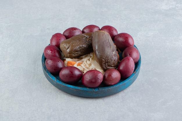 Lekkere zuurkool, aubergine en pruimen op blauw bord.