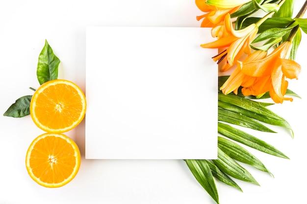 Lelies en sinaasappels in de buurt van bladeren en papier