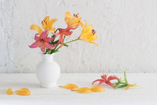 Lelies in witte vaas op witte achtergrond