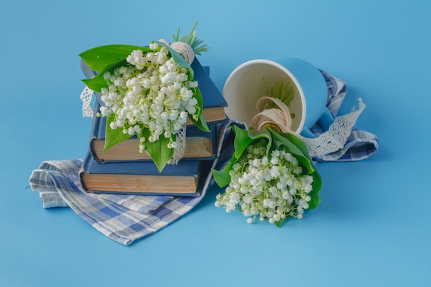 Lelietje-van-dalen en boeken op blauwe achtergrond