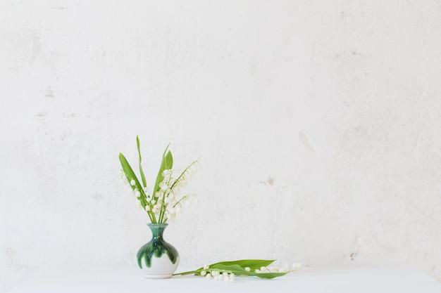 Lelietje-van-dalen in weinig vaas op oude witte muur als achtergrond