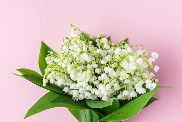 Lelietje-van-dalenbloemen op een pastelroze
