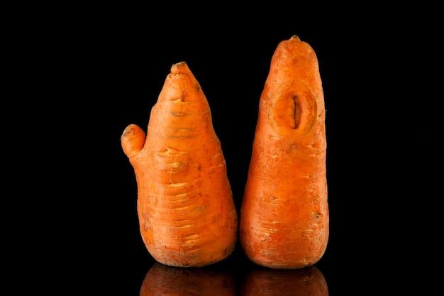 Lelijk eten ongewone groenten grappige planten vervormde biologische wortelen op de zwarte achtergrond