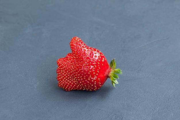 Lelijk fruit. ongewone verse biologische aardbeien. zoals symbool - duim omhoog.