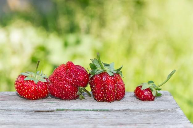 Lelijke aardbeien liggen buiten op een oude houten tafel