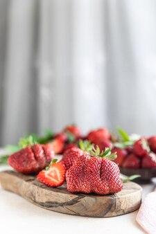 Lelijke biologische aardbeien op houten snijplank trendy lelijk fruit