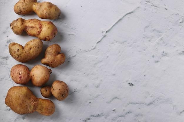 Lelijke biologische abnormale aardappelen op marmeren achtergrond, concept biologische groenten, kopieer ruimte