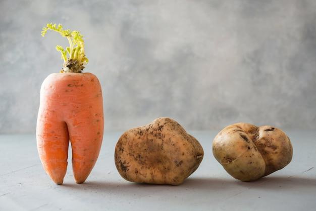 Lelijke biologische groenten, wortel en aardappelen.