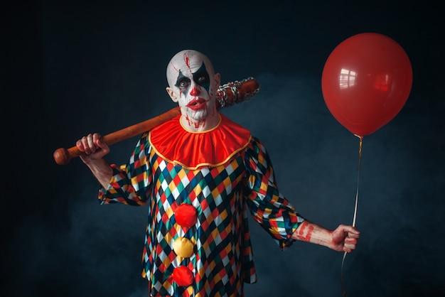Lelijke bloedige clown met honkbalknuppel en luchtballon, horror. man met make-up in carnavalskostuum, gekke maniak