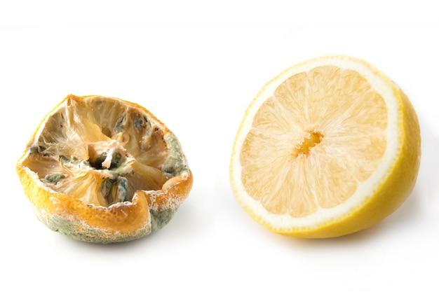 Lelijke citroen met schimmel en verse halve citroen op wit