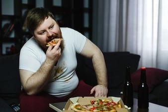 Lelijke dikke man eet pizza zittend op de bank