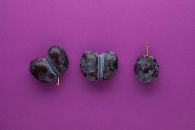 Lelijke dubbele pruimen of pruimen op een paarse achtergrond. ongewoon misvormd fruit kan als voedsel worden gebruikt. ð¡oncept - het verminderen van planten- of voedselverspilling.