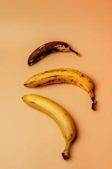 Lelijke fruitmodificatie van drie bananen van rijp tot meer verwend bruin met vlekken