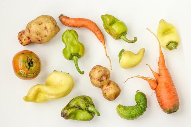 Lelijke groenten: aardappelen, wortelen, komkommer, paprika's en tomaten op witte achtergrond, lelijk voedselconcept, horizontale foto, bovenaanzicht, close-up