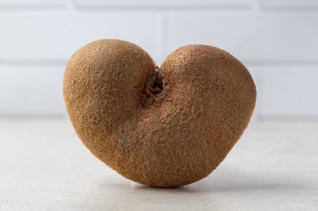 Lelijke hartvormige kiwi's op grijze tafel. biologische misvormde producten. geen afvalconcept
