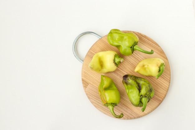 Lelijke organische groene paprika op houten raad