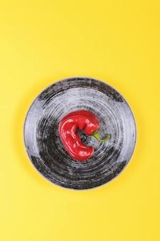 Lelijke rode chilipepers op een zwarte plaat op een gele, minimale stijl van de natuur, pop-art, creatief eten, moderne kunst