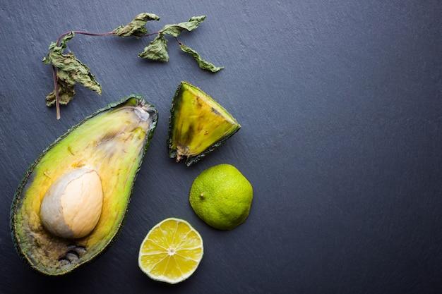 Lelijke rotte avocado op leisteen bord. slechte limoen en droge munt op zwart leisteen bord. rotte tropische vruchten. concept van rot fruit