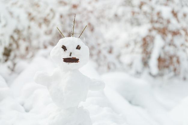 Lelijke sneeuwman in sneeuw bedekt park