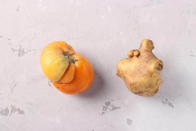 Lelijke tomaat en aardappel op lichtgrijze achtergrond, close-up, lelijk voedselconcept, bovenaanzicht
