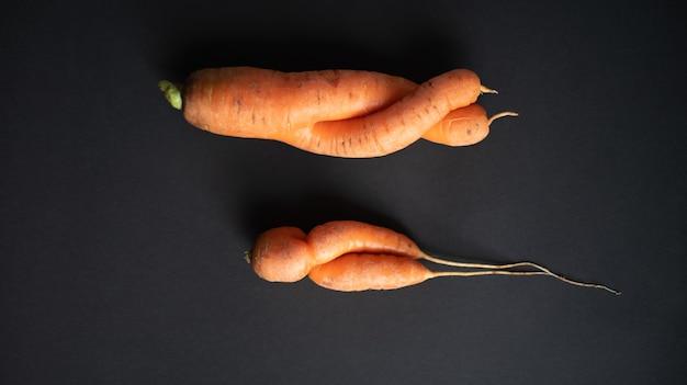 Lelijke wortelen op een donkere zwarte achtergrond bovenaanzicht