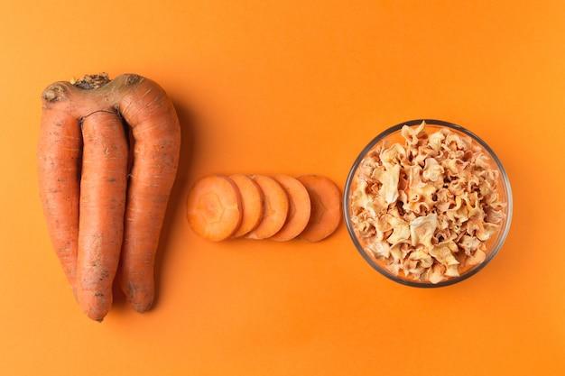 Lelijke wortels, plakjes wortel en chips op een oranje papier oppervlak. de afbeelding toont de mogelijkheid om niet-standaard groenten te gebruiken.