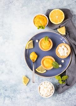 Lemon curd mini taartjes versierd met munt en schijfjes citroen op blauwe keramische plaat. bovenaanzicht.