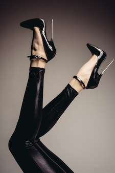 Lenige vrouwenbenen in een spandex catsuit en een fetisjschoen met extreem hoge hakken. bdsm-thema.