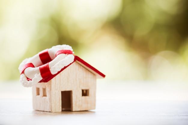 Lening schuld eigendom huis bescherming concept. huis op rode reddingsboei anker