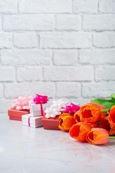 Lente achtergrond met oranje kleurrijke tulpen en geschenkdoos, vrouwen, moederdag, wenskaart, kopieer ruimte afbeelding