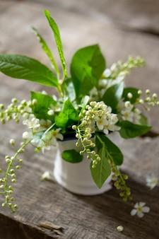 Lente achtergrond. mooie verse witte bloemen van gewone vogelkers op houten achtergrond.