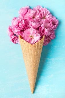 Lente bloeiende kersen roze bloemen in wafel kegel op blauwe achtergrond. minimaal veerconcept. plat lag. bovenaanzicht
