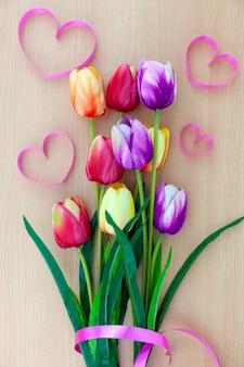 Lente bloem van meerdere kleuren tulpen op hout achtergrond, flat lag afbeelding voor vakantie wenskaart voor moederdag, valentijnsdag, vrouwendag