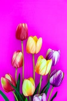 Lente bloem van meerdere kleuren tulpen op roze achtergrond, flat lag afbeelding voor vakantie wenskaart voor moederdag, valentijnsdag, vrouwendag