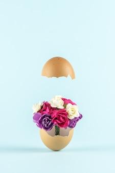 Lente bloemen in gebarsten eierschaal tegen pastel blauwe achtergrond