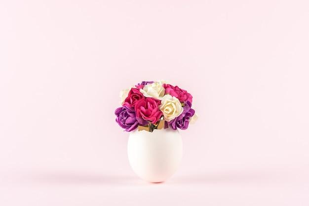 Lente bloemen in gebarsten eierschaal tegen pastel roze achtergrond