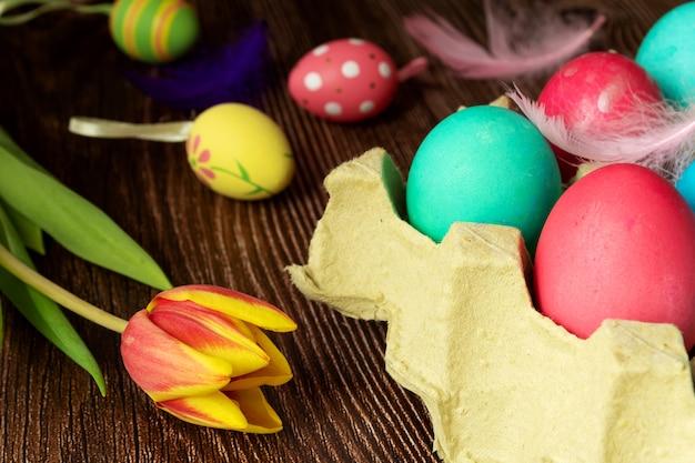 Lente bloemtulp in de buurt van pasen beschilderde eieren op een donkere houten ondergrond