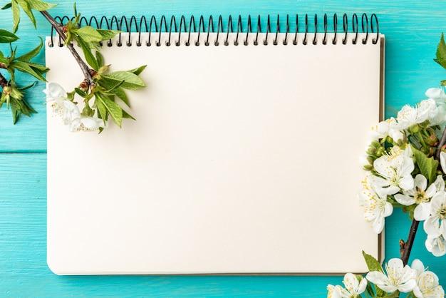 Lente bloesem cherry takken en notebook op blauwe houten achtergrond.
