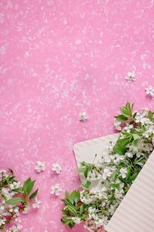 Lente bloesem. kersenbloemen in envelopdoos vlak op pastelkleurachtergrond. wenskaart met witte bloemen, kopie ruimte