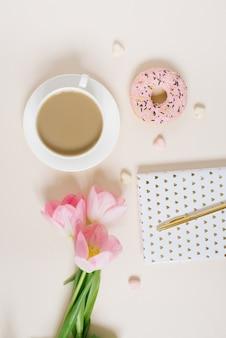 Lente blog-concept. kopje koffie, donut en boeket van roze tulpen op beige achtergrond. platliggend, bovenaanzicht vrouwelijk bureau.