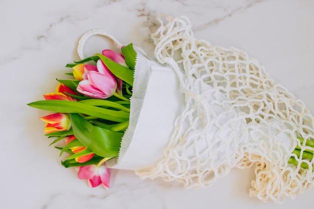 Lente boeket multicolored tulpen in eco zak op een marmeren achtergrond. ruimte kopiëren, plat leggen achtergrond.